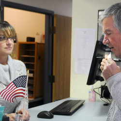 Steve Kalenda seals a ballot Tuesday before handing it over to Monmouth Deputy Town Clerk Kim Dalton. Towns are reporting a higher than normal early voting trend.