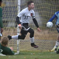 Winslow junior captain forward Jake Warn, middle, leaps over a Mt. Desert Island defender after scoring a goal in a Class B North quarterfinal game Tuesday in Winslow. The second-seeded Black Raiders won, 3-0.