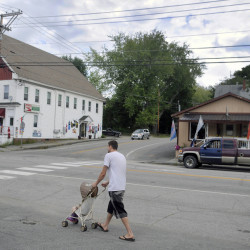 Justin Caouette pushes his daughter, Emily, down Main Street in Monmouth in this September file photo. Monmouth selectmen have approved placing an item on the November ballot, in which voters will decide whether to extend a downtown, tax increment financing district to include five empty lots totaling 99 acres.