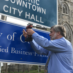 Gardiner Mayor Thom Harnett sets a screw in the city's Certified Business-Friendly sign Thursday on a post near the corner of Brunswick and Dresden avenues.