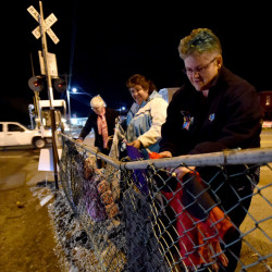 Kelly Roderick, right, Angela Jurdak, center, and Jo Wood hang jackets on the fence Tuesday that runs along the railroad tracks by the intersection of Church and Oak streets in Oakland.
