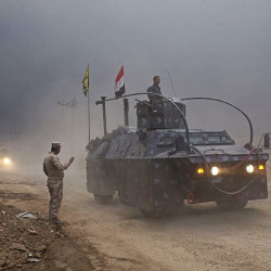 An Iraqi Federal Police vehicle passes through a checkpoint in Qayara, about 30 miles south of Mosul, Iraq, Wednesday, Islamic State militants have been going door to door in farming communities south of Mosul, ordering people at gunpoint to follow them north into the city. Associated Press/Marko Drobnjakovic