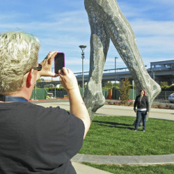 "In this photo taken Wednesday Oct. 19, 2016, art teachers Jo Sutton, left, and Jennifer Jervis, right, take pictures beneath a 55-foot nude statue in San Leandro, Calif. The statue of a naked woman is stirring controversy and a lot of conversation. City officials and the sculptor of the steel nude, which was unveiled this week across from San Leandro's main commuter train stop, say they want to draw attention to ""feminine energy."" Critics say the 13,000-pound towering nude is not appropriate public art. (AP Photo/Jocelyn Gecker)"