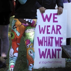 A woman in yoga pants joins others gathering at a starting point before marching in Barrington, R.I., on Sunday.  Associated Press