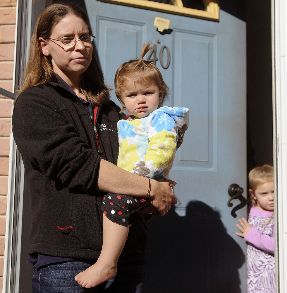 Melissa Shannon, speaking on Tuesday, recalls opening the door early Monday morning at her Winthrop home for a woman who said she needed police. The police later discovered the bodies of Antonio and Alice Balcer, both 47, at 10 Pine Knoll Road. Shannon holds her daughter, Kara, 1, as her daughter Ariana, 3, listens.